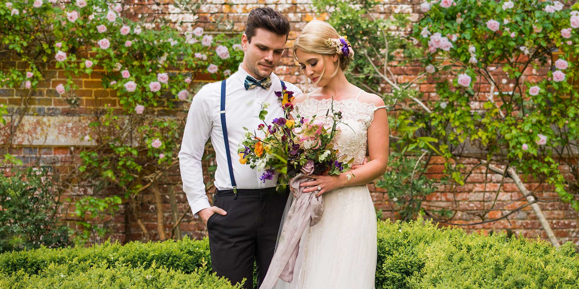 A bride and groom take a walk around the walled gardens at Syrencot on their wedding day